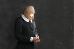 Homem de negócios no terno com Egghead quebrado imagens de stock