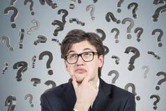 Homem de negócios no terno e os vidros e os pontos de interrogação 3d Fotos de Stock