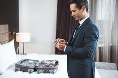 Homem de negócios no terno formal usando o smartphone na sala de hotel com mala de viagem aberta foto de stock