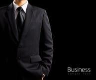 Homem de negócios no terno no fundo preto Fotografia de Stock