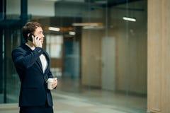 Homem de negócios no terno preto que fala no telefone e no café afastado bebendo imagem de stock