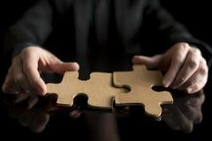 Homem de negócios no terno preto que guarda duas partes de harmonização do enigma Fotografia de Stock Royalty Free