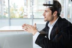 Homem de negócios no terno preto que senta-se no escritório Foto de Stock Royalty Free
