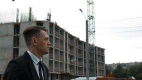 Homem de negócios no terno que anda perto da construção recentemente construída vídeos de arquivo
