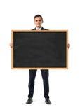 Homem de negócios no terno que está e que guarda o quadro-negro no quadro de madeira, isolado no fundo branco Imagem de Stock Royalty Free