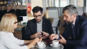 Homem de negócios no terno que faz a oferta do negócio aos sócios durante o encontro no café video estoque