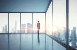 Homem de negócios no terno que olha o nascer do sol na cidade 3d rendem Fotografia de Stock Royalty Free