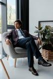 homem de negócios no terno que olha para fora a janela ao descansar na poltrona fotos de stock royalty free