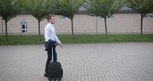 Homem de negócios no trabalho O homem novo considerável na camisa branca anda de um aeroporto com uma mala de viagem vídeos de arquivo