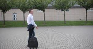 Homem de negócios no trabalho O homem novo considerável na camisa branca anda de um aeroporto com uma mala de viagem filme