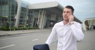 Homem de negócios no trabalho O homem novo considerável na camisa branca anda de um aeroporto com uma mala de viagem e fala no te video estoque