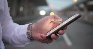 Homem de negócios no trabalho O homem novo considerável na camisa branca e o braço rico olharem tipos um número em seu smartphone filme