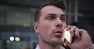 Homem de negócios no trabalho O homem novo considerável na camisa branca fala no telefone e olha em torno dele para um táxi filme
