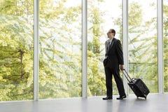 Homem de negócios no vestuário formal preto que guarda o saco do trole Fotos de Stock Royalty Free