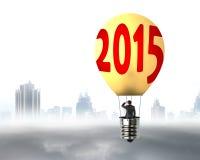 Homem de negócios no voo brilhantemente amarelo do balão de ar quente da lâmpada 2015 Fotografia de Stock Royalty Free