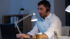 Homem de negócios nos auriculares com o portátil no escritório da noite filme
