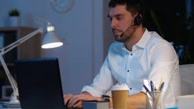 Homem de negócios nos auriculares com o portátil no escritório da noite video estoque