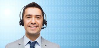Homem de negócios nos auriculares sobre o símbolo de moeda do dólar Imagem de Stock Royalty Free