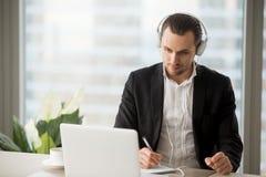 Homem de negócios nos fones de ouvido que tomam notas na frente do portátil Imagem de Stock Royalty Free