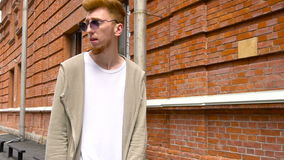 Homem de negócios novo à moda com barba vermelha, nos óculos de sol e no hoodie branco andando ao longo da parede de tijolo video estoque
