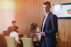Homem de negócios novo à moda que veste um revestimento e uma camisa no fundo de um escritório de trabalho com os povos que tr fotografia de stock royalty free