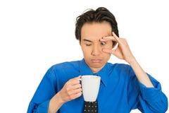 Homem de negócios novo adormecido de queda cansado que guarda a xícara de café imagens de stock royalty free