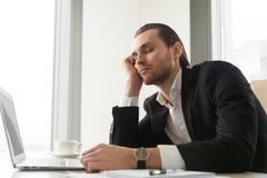 Homem de negócios novo aplanado na frente do portátil no trabalho imagem de stock royalty free