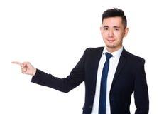 Homem de negócios novo asiático com ponto do dedo de lado Imagem de Stock