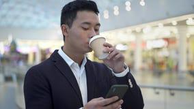 Homem de negócios novo asiático no café bebendo do terno que texting no telefone filme