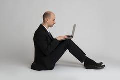 Homem de negócios novo assentado com portátil foto de stock royalty free