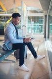 Homem de negócios novo assentado no aeroporto que verifica uma tabuleta e um Ca foto de stock royalty free