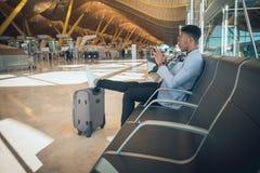 Homem de negócios novo assentado no aeroporto que verifica uma tabuleta e um Ca foto de stock