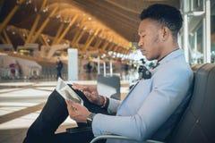 Homem de negócios novo assentado no aeroporto que verifica uma tabuleta e um Ca imagens de stock