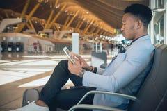 Homem de negócios novo assentado no aeroporto que verifica uma tabuleta e um Ca fotografia de stock