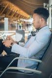 Homem de negócios novo assentado no aeroporto que verifica uma tabuleta e um Ca imagem de stock