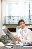 Papel atrativo da leitura do homem de negócios no café. fotografia de stock
