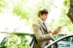 Homem de negócios com carro e smartphone. foto de stock royalty free