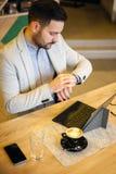 Homem de negócios novo bem sucedido que olha seu relógio, trabalhando no café foto de stock
