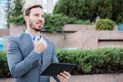 Homem de negócios novo bem sucedido que trabalha em uma tabuleta na frente de um prédio de escritórios Guardando a mão no queixo  imagens de stock royalty free