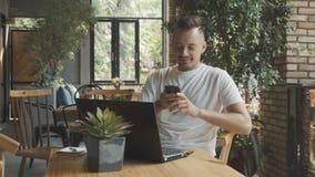 Homem de negócios novo caucasiano que conversa com a amiga no café moderno durante o trabalho em linha no laptop Uso do homem vídeos de arquivo