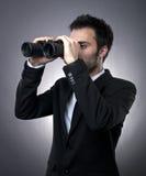 Homem de negócios novo com binóculos Fotos de Stock Royalty Free