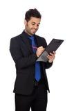 Homem de negócios novo com laço azul com uma prancheta Fotos de Stock