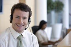 Homem de negócios novo com os auriculares no escritório Imagem de Stock Royalty Free