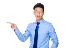 Homem de negócios novo com ponto do dedo de lado Imagens de Stock Royalty Free