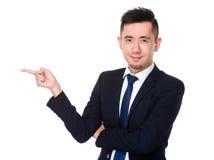 Homem de negócios novo com ponto do dedo de lado Fotos de Stock Royalty Free