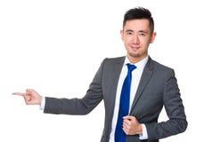 Homem de negócios novo com ponto do dedo de lado Foto de Stock Royalty Free