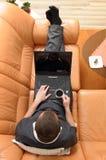 Homem de negócios novo com um portátil na bebida do sofá Fotografia de Stock Royalty Free