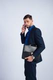 Homem de negócios novo com uma pasta e um telefone Imagens de Stock