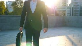 Homem de negócios novo com uma pasta que anda na rua da cidade Homem de negócio que comuta para trabalhar no ambiente urbano filme