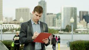 Homem de negócios novo com uma tabela plana em uma rua vídeos de arquivo